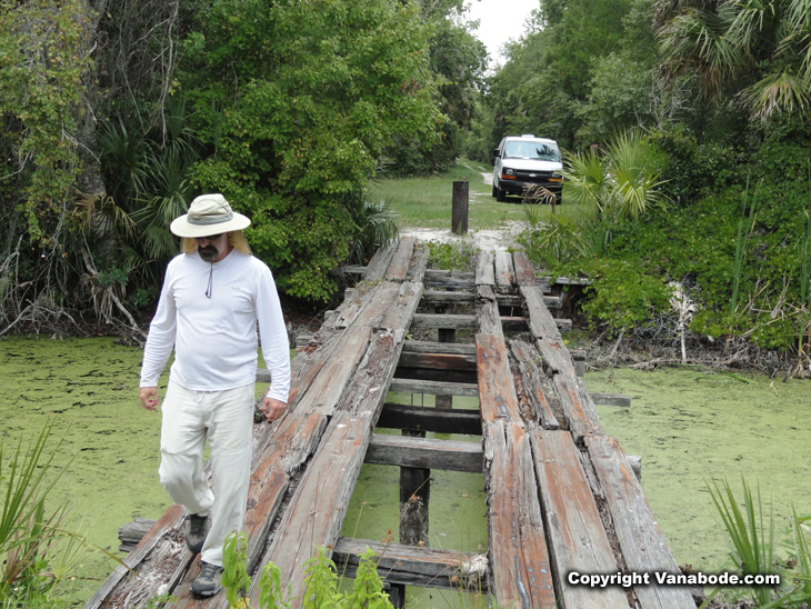 vanabode author jason odom crossing a footbridge in the tosohatchee wildlife management area of florida